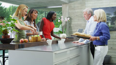 Happy group of family & friends preparing a meal with freshly baked bread - stock footage