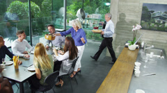 Happy group of family & friends eating together and drinking wine in modern home - stock footage