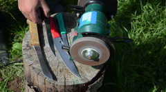 Hand sharpening knife with electric grinder  tool on outdoor log Stock Footage