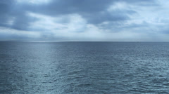 Stock Video Footage of Rippled and calm sea with far mountains/islands on the horizon, rainy clouds
