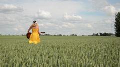 Pretty girl in dress headscarf play guitar walk in wheat field Stock Footage