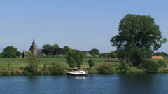 River Meuse, The Netherlands + church tower and village behind river dike Stock Footage