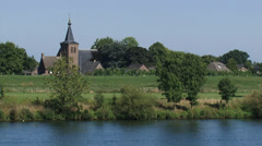 Church tower Dutch village of Niftrik behind river dike + zoom out river Meuse Stock Footage