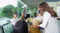 Happy group of family & friends sit down to eat a meal together in modern home - stock footage