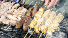 Kebabs being turned on a grill Stock Footage