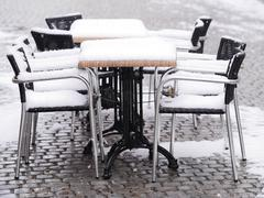 snowy chairs tables winter - stock photo
