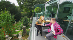 Romantic couple enjoying a meal outdoors get up to take a look at the view Stock Footage