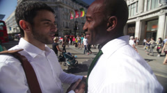 Businessmen meet and shake hands outdoors in area of central London, UK - stock footage