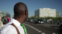 Businessman at the side of London city road trying to hail a cab - stock footage