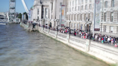 Crowded tourist area beside the River Thames in London Stock Footage