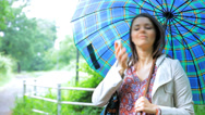 Woman with umbrella having funny conversation on the phone Stock Footage