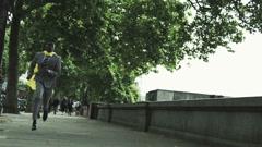 Superhero businessman runs across bridge in London UK Stock Footage