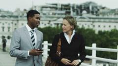 Businessman and woman walk along a city bridge talking business. Stock Footage