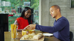 Happy attractive young couple preparing a meal and sitting down to eat Stock Footage