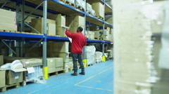 Worker moving consignment in a warehouse - stock footage