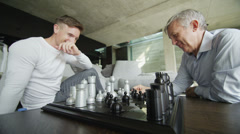 Two men play a game of chess with contemporary chess set Stock Footage