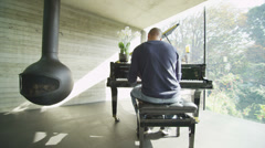 Young man plays the piano alone in contemporary home with sunlight streaming in Stock Footage