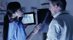 Doctor and nurse or surgeons in meeting. A touch screen device is central to the - stock footage