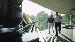 Mature man plays the piano in contemporary home as his partner listens - stock footage