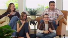 Family at home watching television and celebrating - stock footage