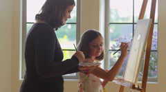 Woman and daughter painting together - stock footage