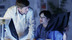 Medical personnel examining patient x rays Stock Footage