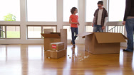 Stock Video Footage of Family in new home unpacking boxes together