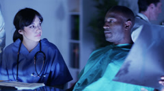 Medical personnel examining patient x rays - stock footage