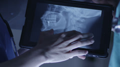 Doctor and nurse or surgeons in meeting. A touch screen device is central to the Stock Footage