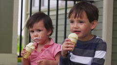 Young brother and sister eating ice cream on porch Stock Footage