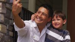 Father and son take self portrait together - stock footage