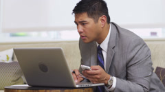 Business man in office lobby using laptop and cell phone - stock footage