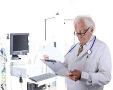 doctor in pulmonary function lab looking at a clipboard - stock photo
