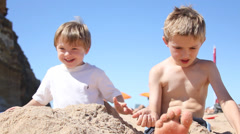 Cute brothers playing in the sand on summer beach holiday Stock Footage