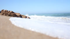 Ocean waves breaking against the shore on a clear blue summer day Stock Footage