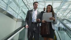 Business people going down escalator Stock Footage