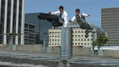 Two businessmen jump over barrier, slow motion Stock Footage