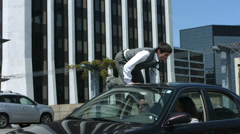 Business man vaults over car in parking lot Stock Footage