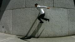 Business man jumps off wall, slow motion Stock Footage