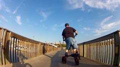 Bike Following Trikke Across Wooden Bridge- Newport Beach CA Stock Footage