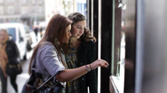 Happy young female friends window shopping in the city of Edinburgh, Scotland - stock footage