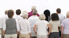 Group of senior people coming together to form a happy close group of Stock Footage
