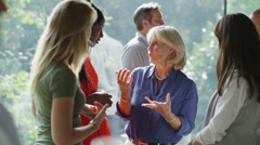 Female friends or casual business colleagues chatting together at a social event Stock Footage