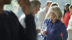 Attractive mature couple chatting and flirting together at a social gathering. - stock footage