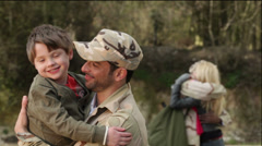 Army soldier returning home to the embrace of his family - stock footage