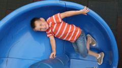 Portrait of boy on slide at school playground Stock Footage