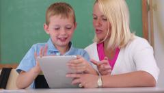 Teacher and student use digital tablet in classroom - stock footage
