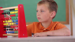 Boy at school counting with abacus Stock Footage