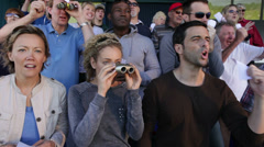 Enthusiatic crowd of spectators at horse racing or dog track. - stock footage