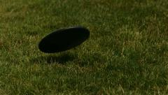 Closeup of discus landing in grass, slow motion Stock Footage